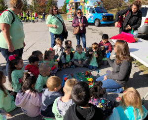 """Jamie Dove of the Jackson County planning and zoning office and Keep Jackson Beautiful talked with children and adults from West Jackson Elementary School about pollution and litter using a table top """"community"""" model -- with soil and groundwater pollution created with powdered hot cocoa."""