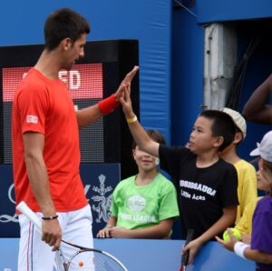 Tennis star Novak Djokovic gives a high five to a young fan