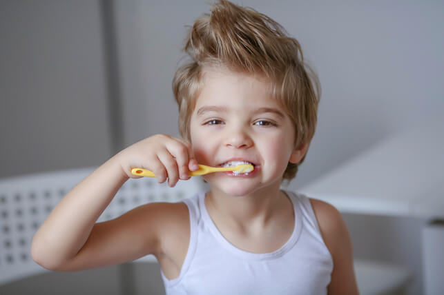 child with bedhead brushing his teeth 2