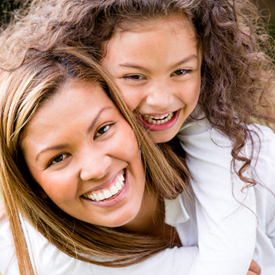 smiling child piggybacking on her mom 2