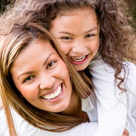 smiling child piggybacking on her mom 2