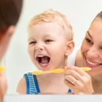 mom brushing her toddlers teeth 3