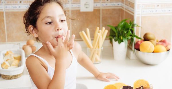 child licking her fingers while snacking 2