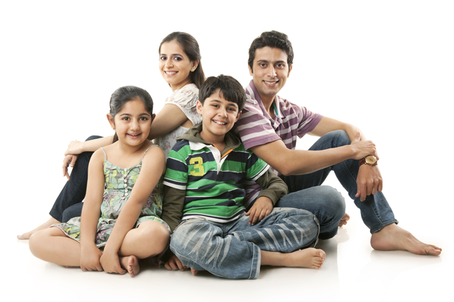 smiling family of four sitting on floor barefoot 2