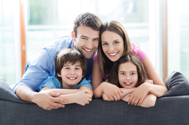 smiling family of four on a couch