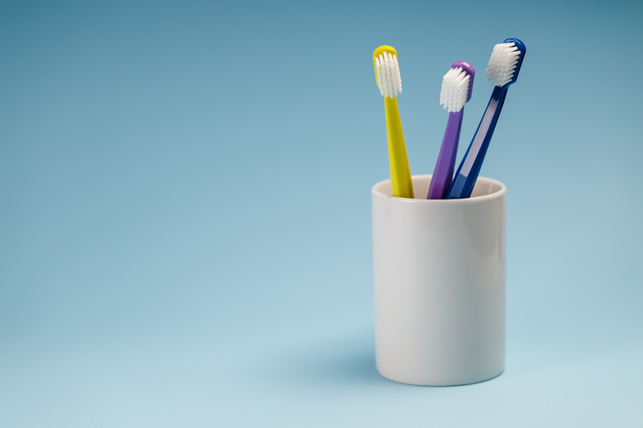 three toothbrushes in a ceramic container