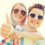 smiling teens piggybacking in sunglasses 2