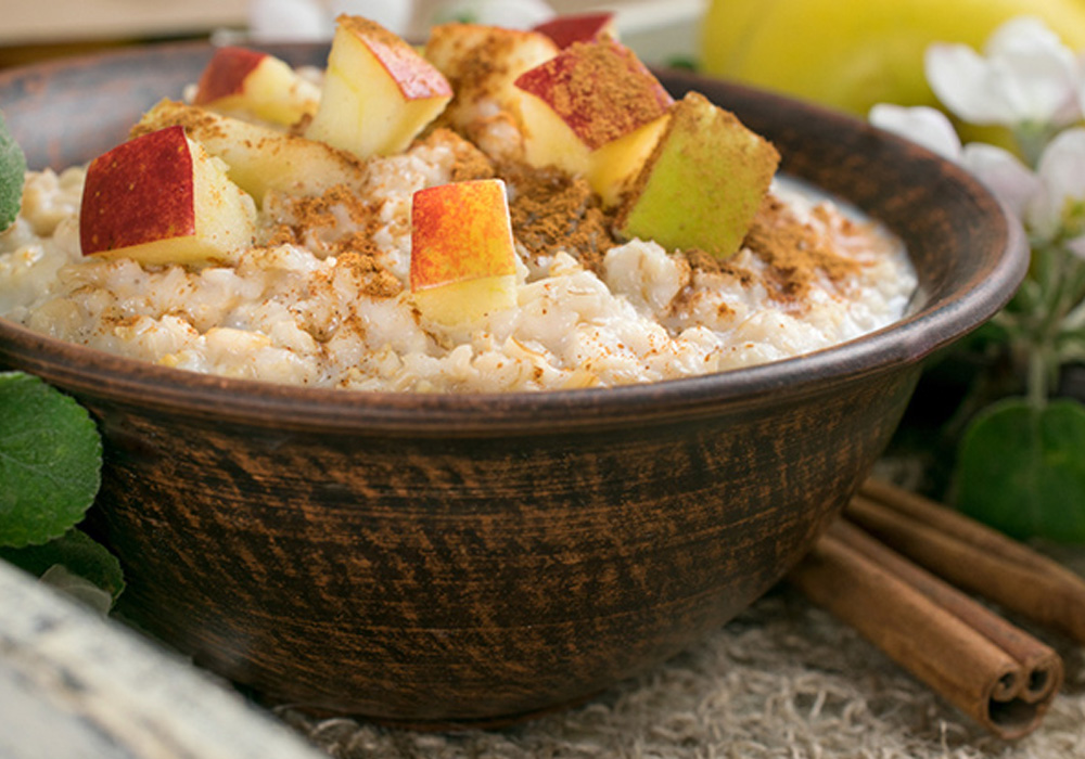 bowl of oatmeal with slices apples and cinnamon