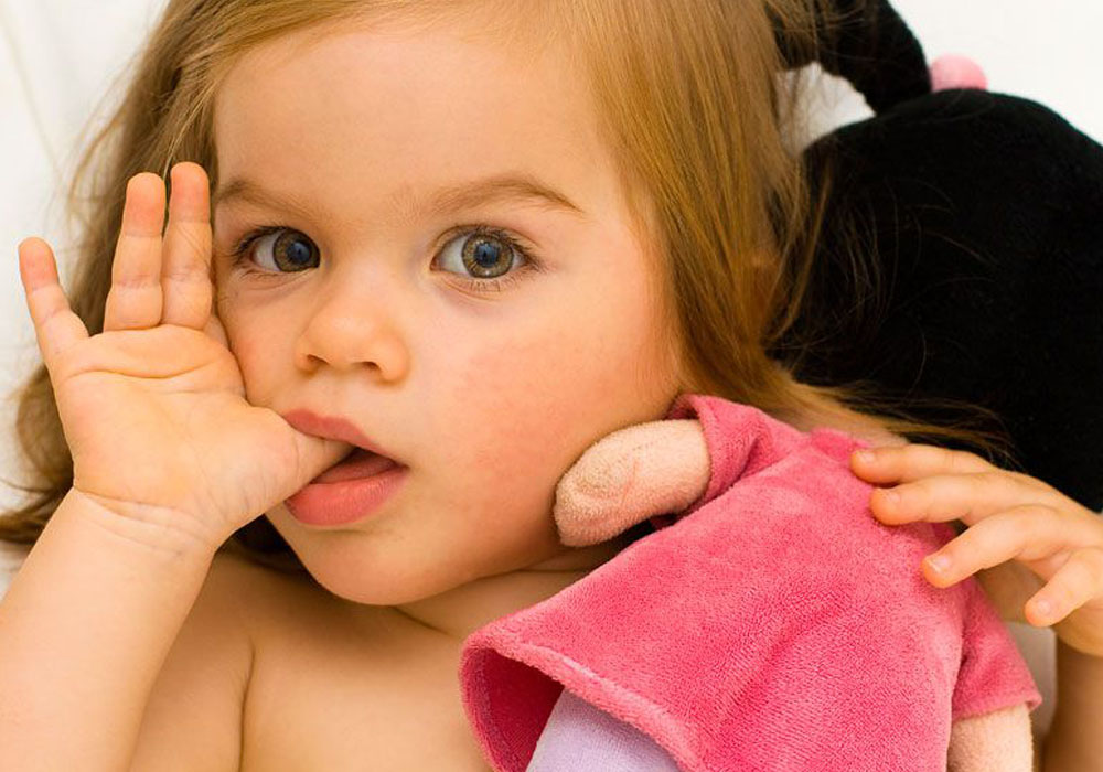 toddler holding a doll while sucking her thumb