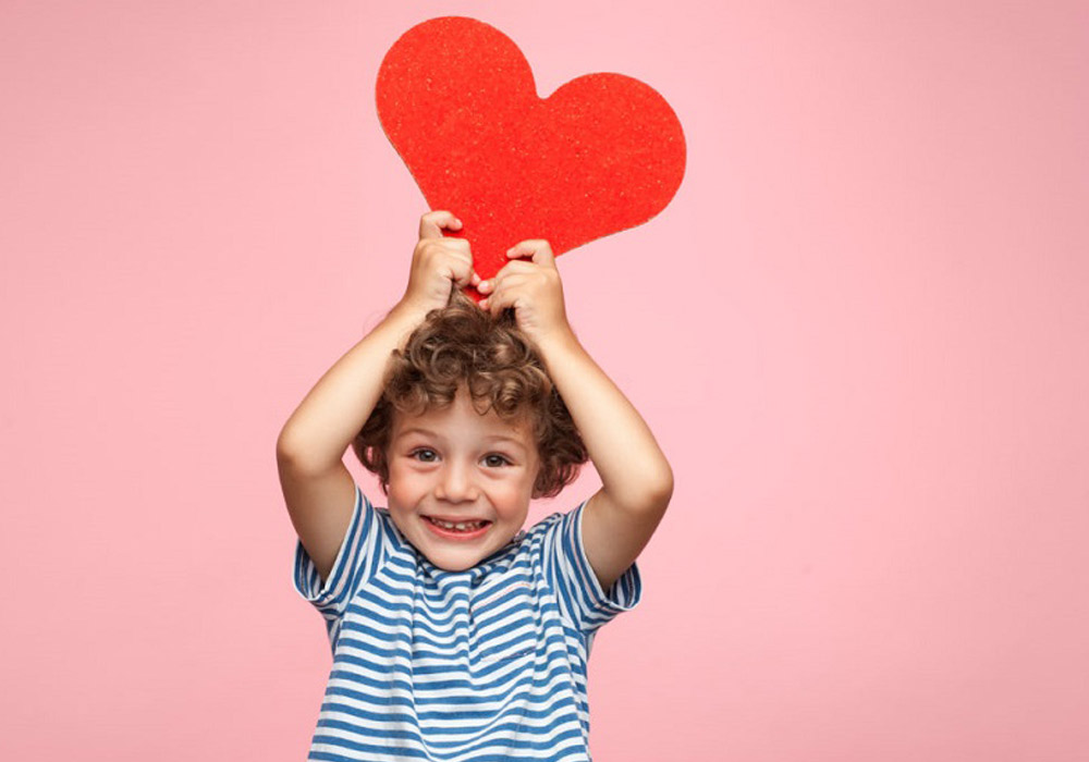 child holding a heart cut out above his head