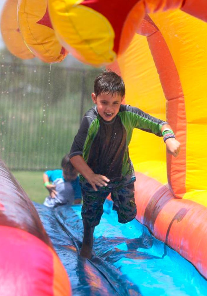 Child playing in inflatable water bounce house