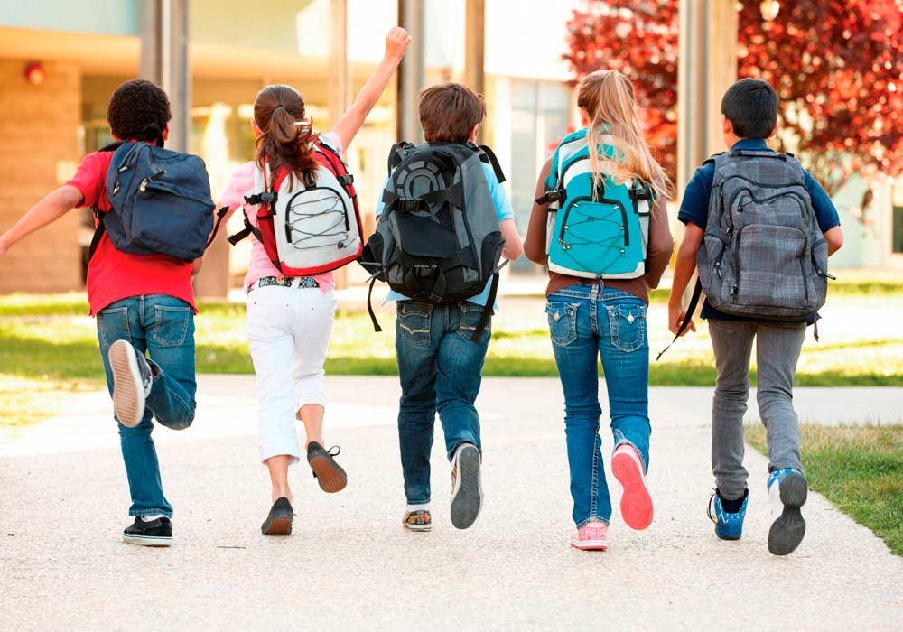 five children with backpacks walking toward school
