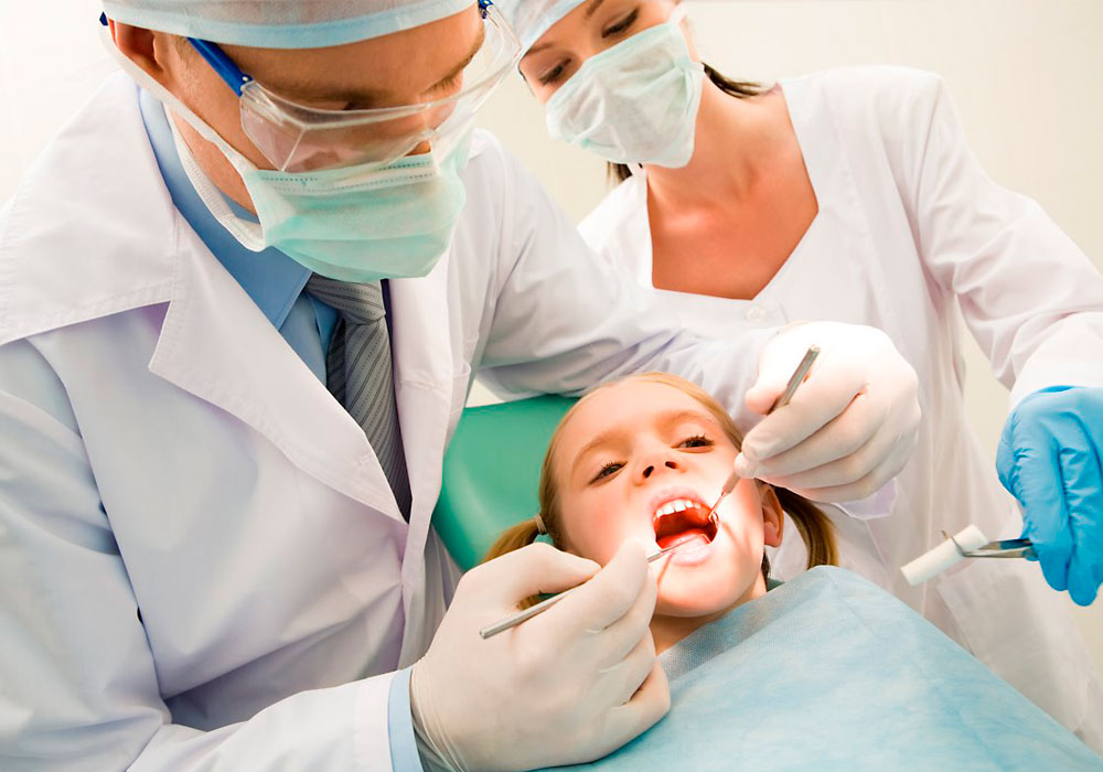 child getting cleaning by dentists
