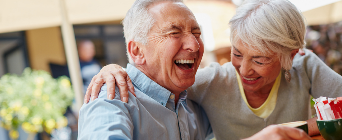 photo of senior couple sharing a laugh at a coffee shop