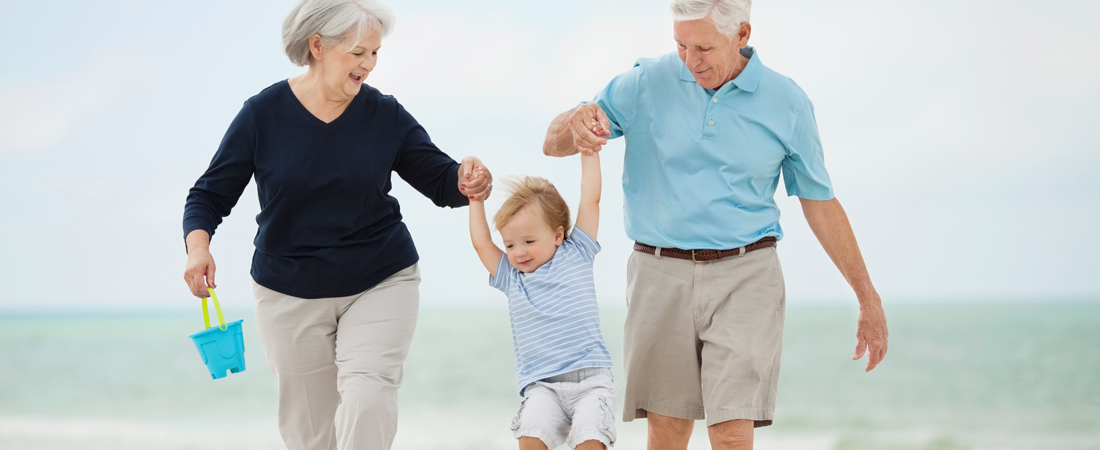 photo of grandparents swinging their grandson with the ocean in the background