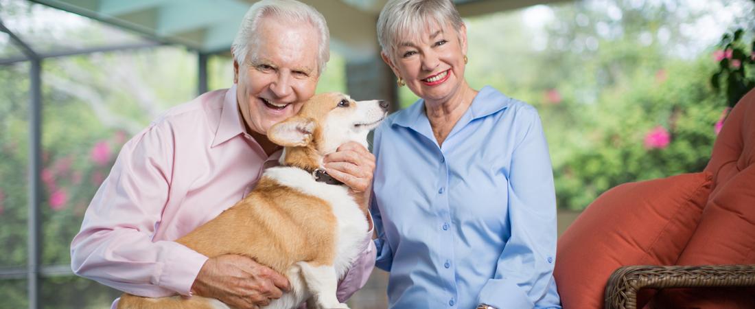 photo of smiling senior couple with their corgie dog