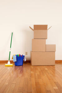 Cleaning and moving supplies. Cardboard boxes and a mop in an empty room.Please also see: