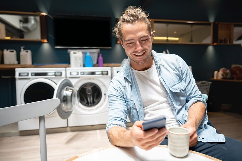 Handsome-young-man-drinking-coffee-and-looking-at-smartphone-while-waiting-at-the-laundromat-mc
