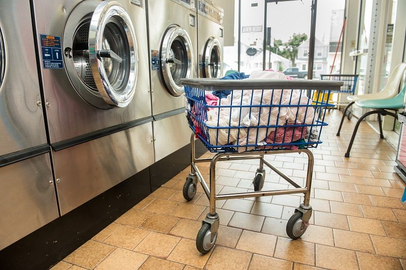 Industrial-washing-machines-in-public-laundromat,-with-laundry-in-basket-cm
