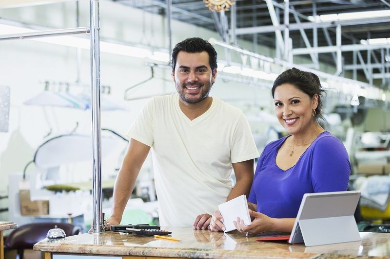 Hispanic-small-business-owners,-dry-cleaner-paying-bills--m