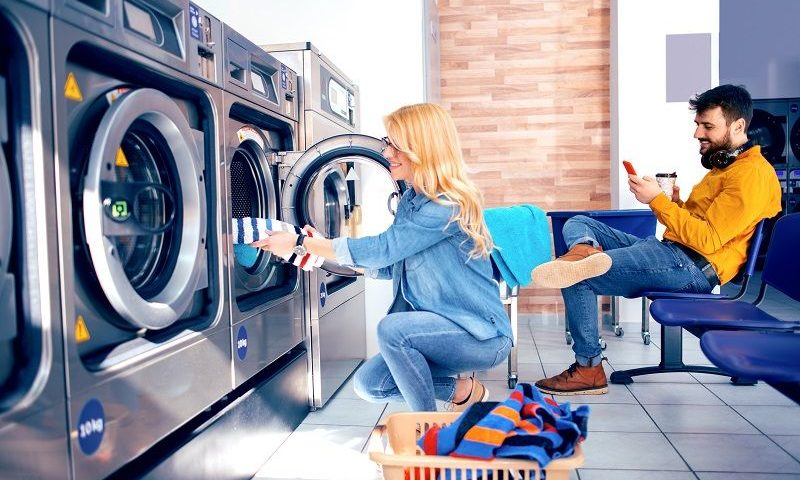 Young-cheerful-couple-doing-laundry-together-at-laundromat-shop-cm-800x480