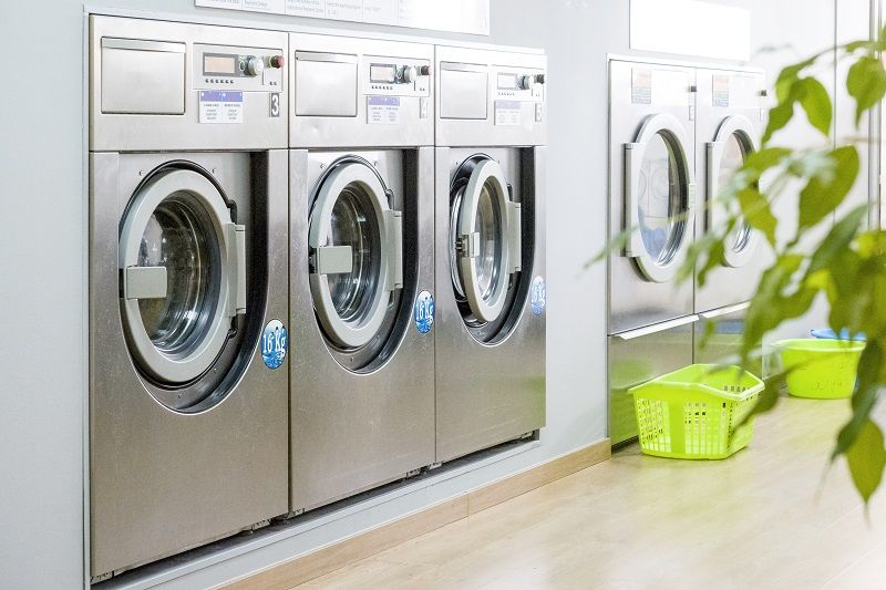 Public-laundry-with-modern,-silver-washing-machines--cm