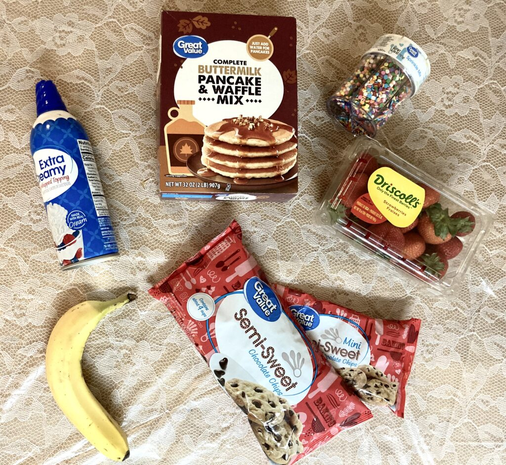 Ingredients, including pancake mix, strawberries, bananas, whipped cream, chocolate chips, and sprinkles.