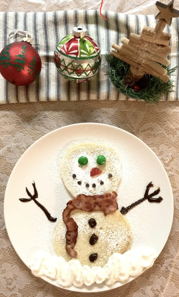 Snowman pancake with powdered sugar and candy decorations