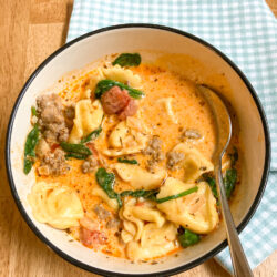 Bowl of tortellini soup on wooden table