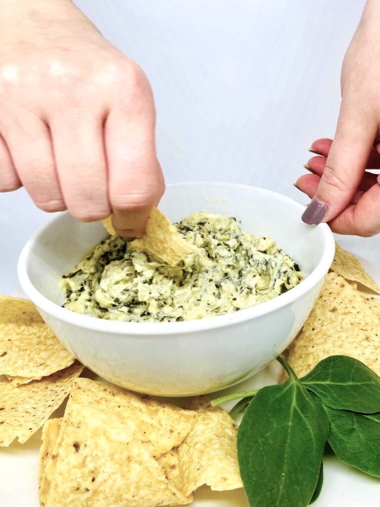 A chip being dipped into a bowl of Instant Pot spinach artichoke dip