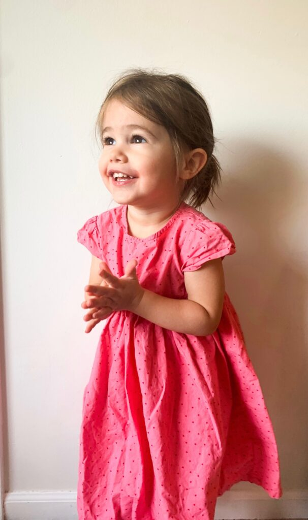 Toddler in pink Three Little Peas dress