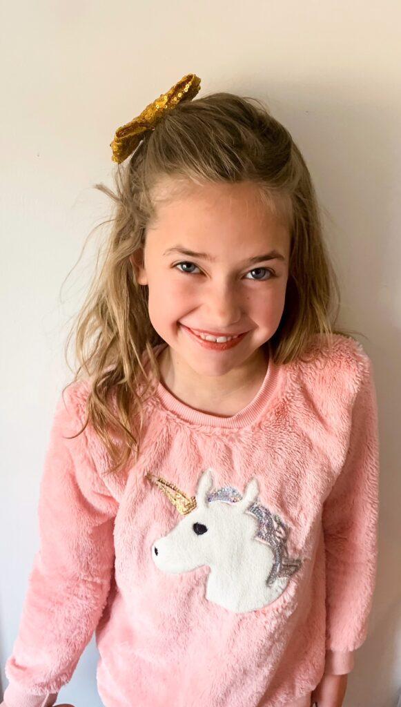 Preteen girl in Three Little Peas unicorn sweater