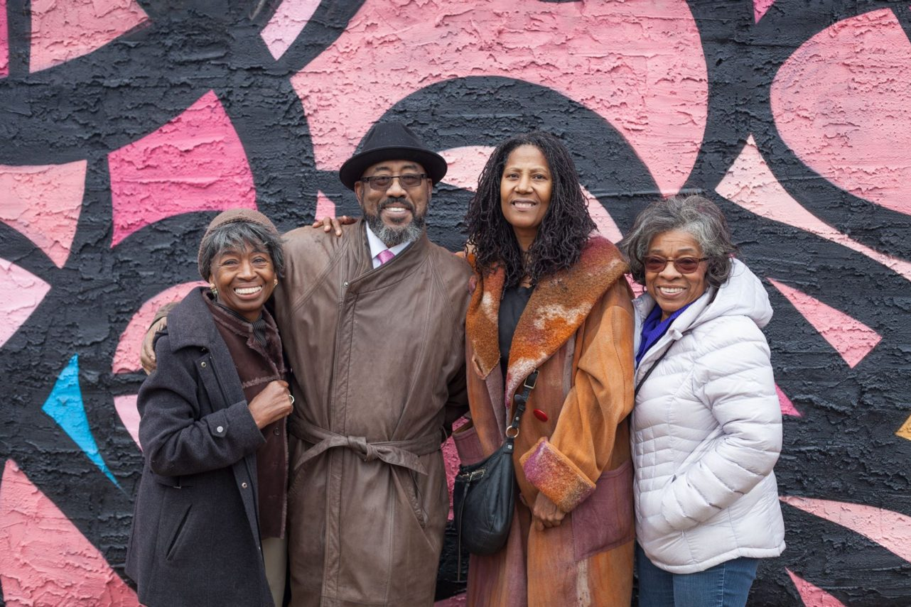 """West Powelton residents -- Ardie, Kernard, Pam, and Patricia -- at the opening dedication of """"Soul of the Black Bottom"""" mural by eL Seed. Photo by Chip Colson."""