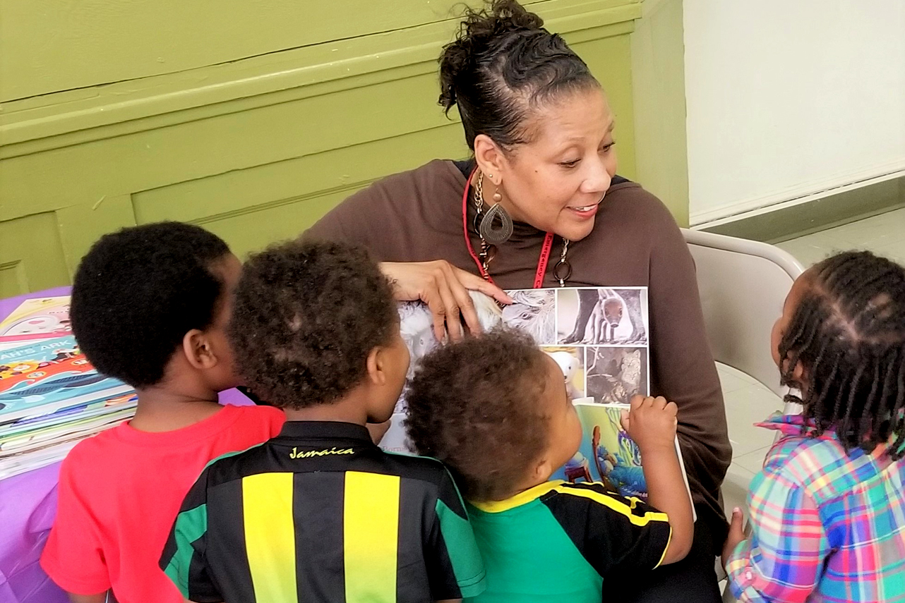 Early Childhood Education Specialist Dawn Nock (from PEC's BELL project) reading to children