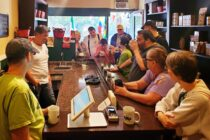Ten people gather around the long wooden counter at 9th Street Coffee & Tea. Jake, behind the counter in a white shirt, tells the group about his company.