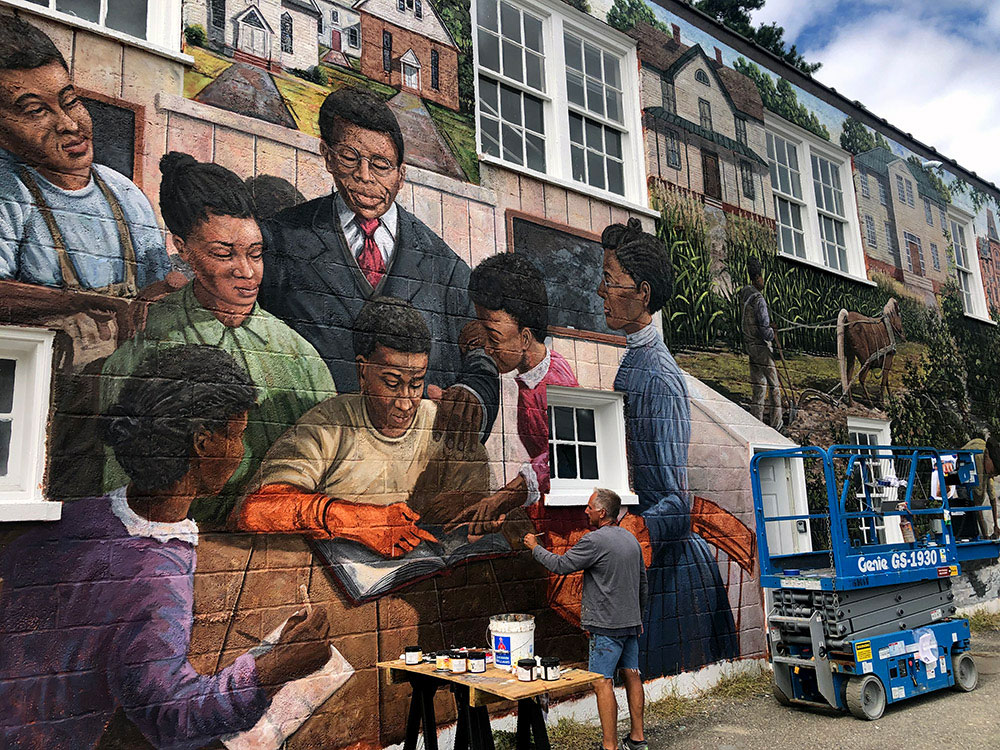 Artist adding detail to TC Walker mural