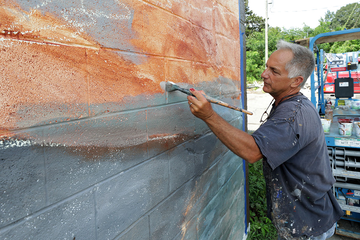 Painter and artist Michael Rosato continues work on the TC Walker mural in downtown Gloucester