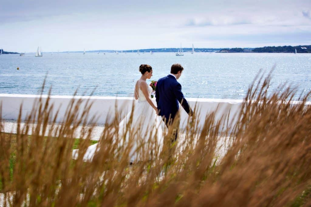 Bride and Groom Holding Hands by Waterside