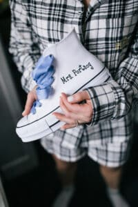 Bride Holding Canvas Sneakers with Blue Ribbon