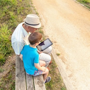 Grandfather and grandson looking at iPad
