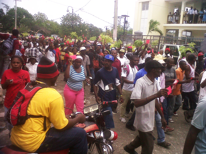 As another way to signal their opposition to Martelly, the Haitian masses march with red cards, which, when given to a player by a football (soccer) referee, mean he's out for that match and the next. The people are telling Martelly to get out. [Haiti Action Committee]