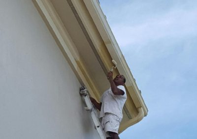 Painting Marco Island house eaves and rain gutter
