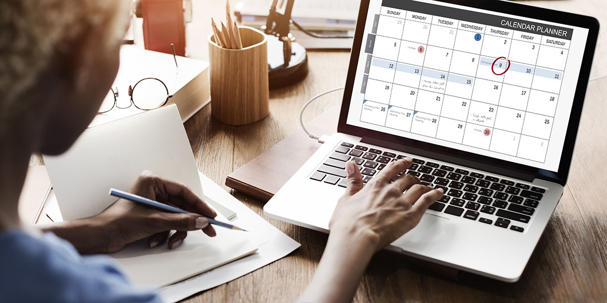 person at a laptop looking at a calendar