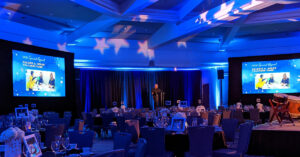 ballroom set for gala event with multiple screens, blue lighting and stars projected on the ceiling