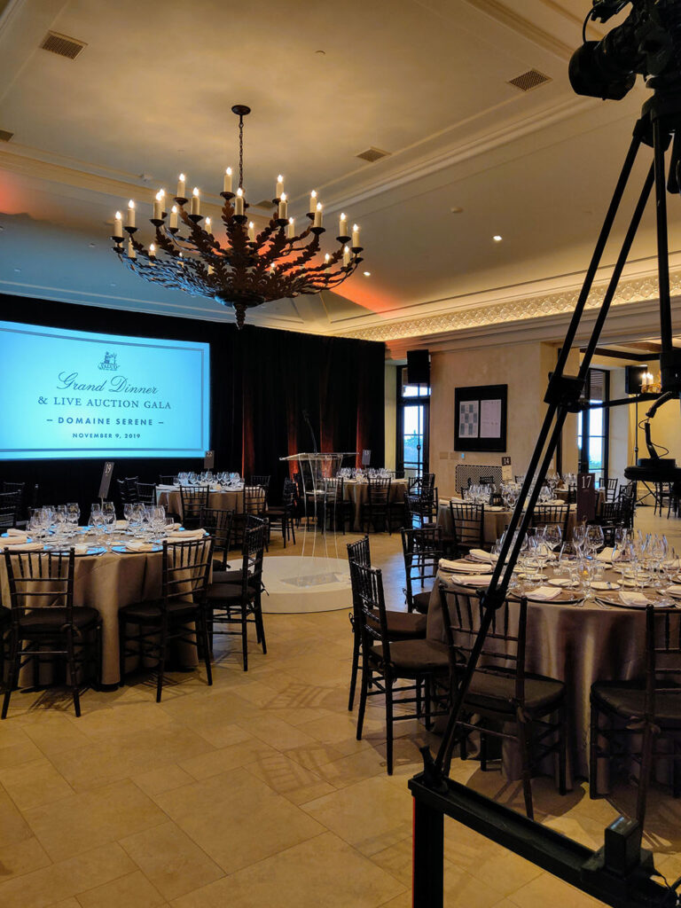 roud tables and chairs are set for dinner in ballroom. There is a large screen and a camera in view.