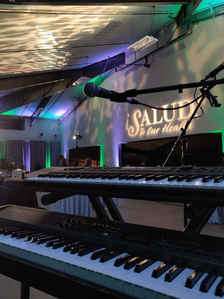 looking past two keyboards and a microphone to see green and purple lighting and the Salud logo projected on the wall
