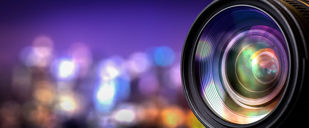 close up of the front of a camera lens against a colorful, blurred background