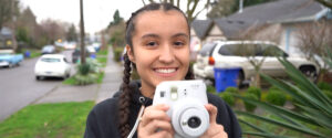 a girl, smiling and holding a camera outside in a neighborhood