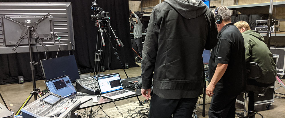 cameras, monitors, and a backdrop set up in a warehouse space to test live streaming