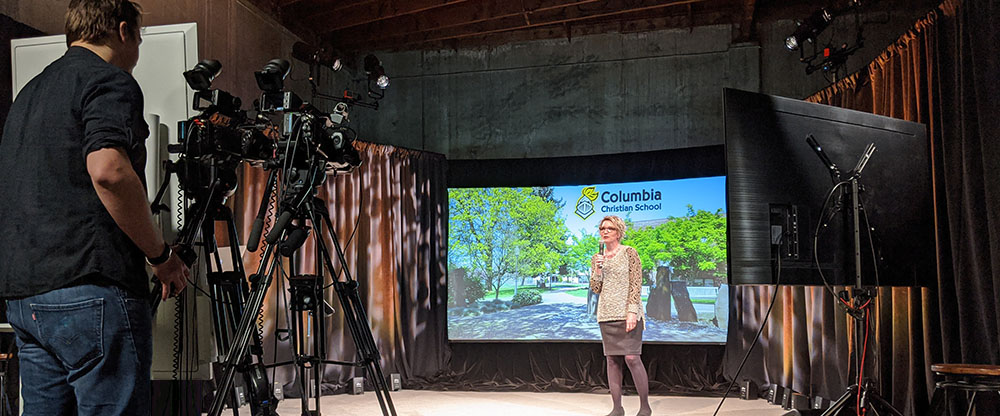 a virtual event host is speaking in front of a camera